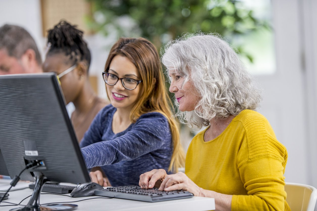 Young girl helping a woman at a computer
